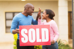 cheerful young black couple holding sold sign and celebrating their house been sold