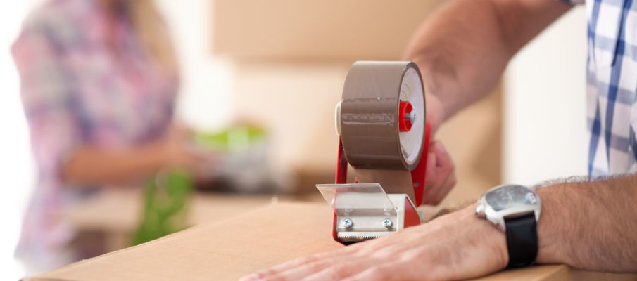 close up of male hand packing cardboard box