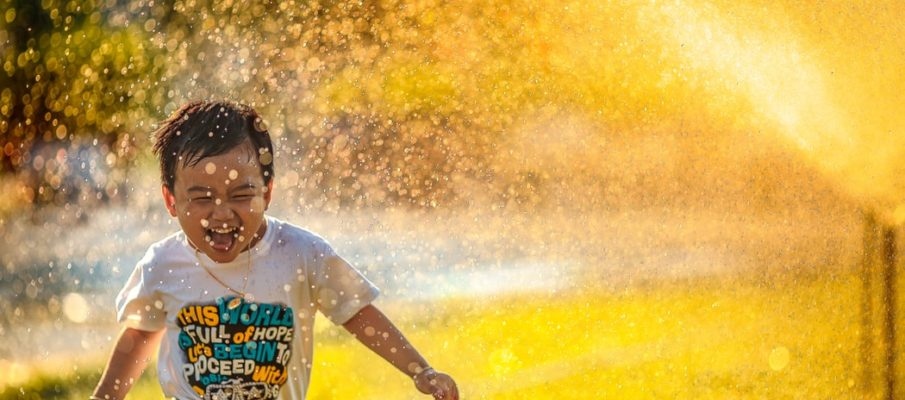 boy laughing in water sprinkler